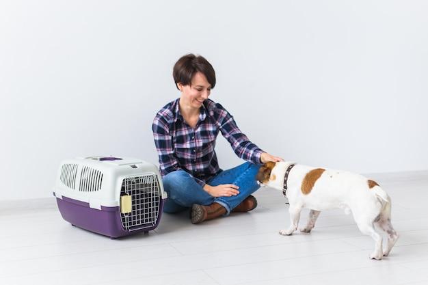 가방 및 애완 동물 소유자 개념을 들고 개-격자 무늬 셔츠에 매력적인 쾌활한 여성이 좋아하는 보유