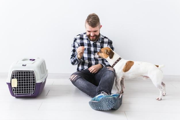 犬のキャリーバッグとペットの飼い主のコンセプト-格子縞のシャツを着た魅力的な陽気な男性がお気に入りを保持します