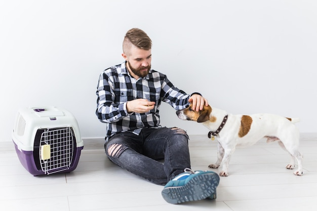 Dog carrying bags and pets owner concept - attractive cheerful male in plaid shirt holds favourite