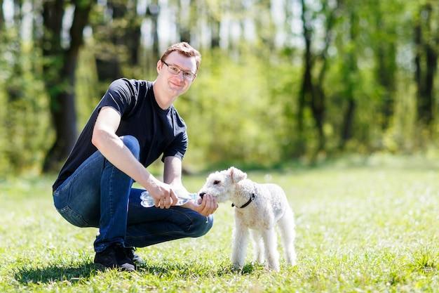 夏の暑さの間に男性の手から水を飲む犬