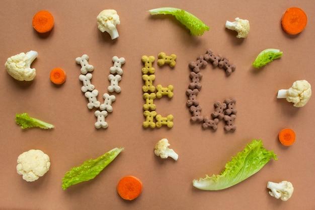 Собачьи сухарики в виде косточки буквенное обозначение veg. морковь, цветная капуста и салат на бежевом фоне. хрустящие вегетарианские лакомства и питание для щенков.