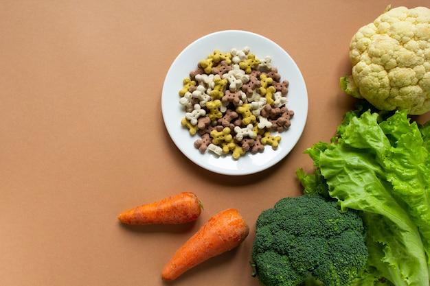 Собака сухие хрустящие кости в виде кости на белой тарелке. цветная капуста, брокколи, морковь и салат на бежевом фоне. скопируйте пространство и плоскую планировку.