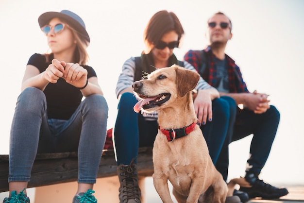 Dog and family sitting outdoor on a wooden deck