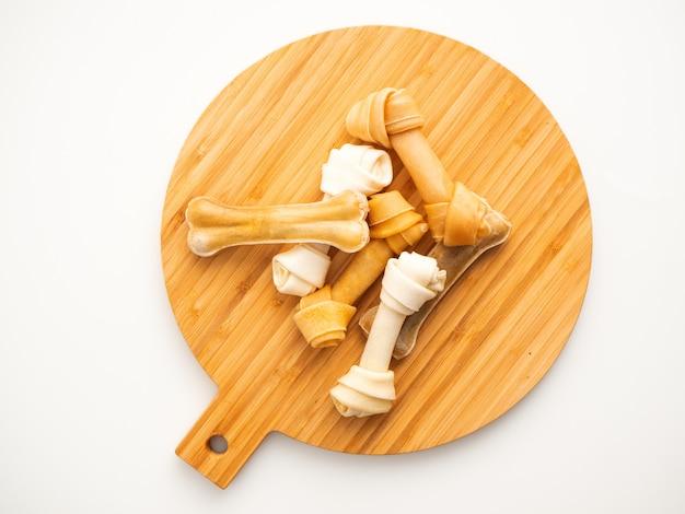 Dog food bone on chopping wood on white