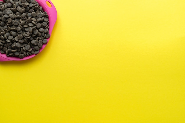 Dog food in a pink bowl in the upper left corner. flat lay, top view. space for text.