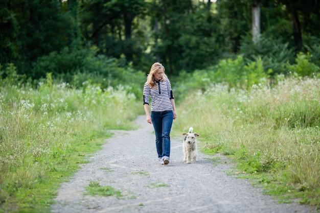 Собака фокстерьер с женщиной по тропинке после тренировки