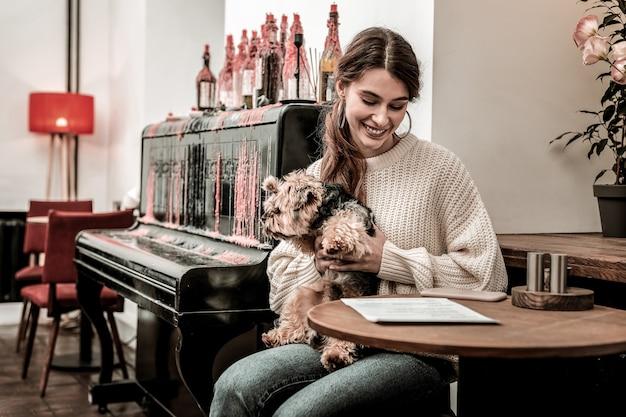 犬に優しいカフェ。若い女性が犬と一緒にカフェに来ました