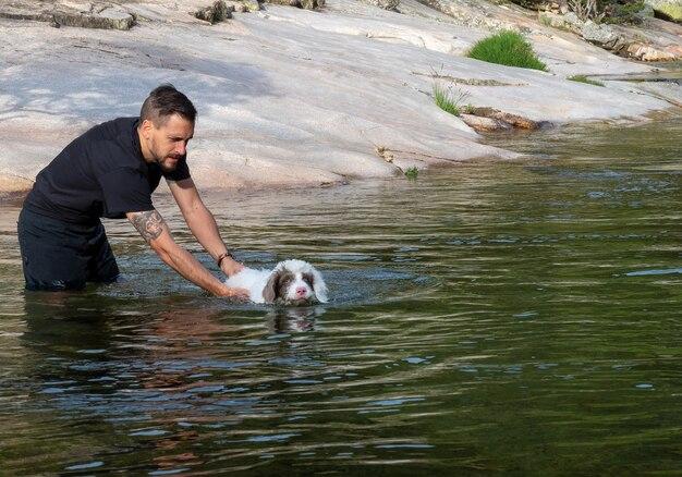 子犬にラグーンで泳ぐように教える犬のハンドラー。湖で泳ぐことを学ぶ白い子犬。