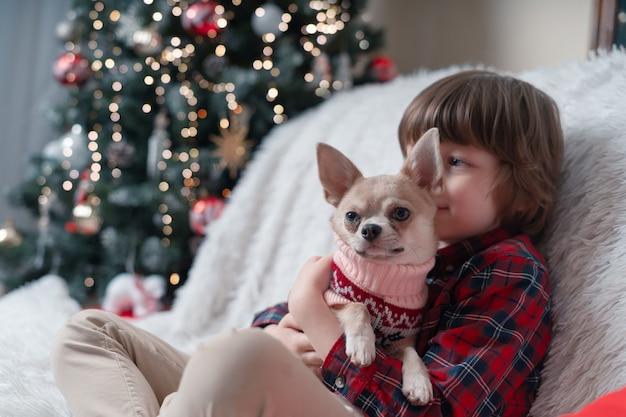 クリスマスにセーターを着た犬が子供を抱きしめます。