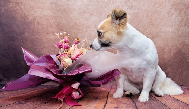 The dog is sitting next to a bouquet of flowers on a beautiful vintage