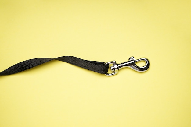 Dog leash with carabiner on a yellow background, flat lay.