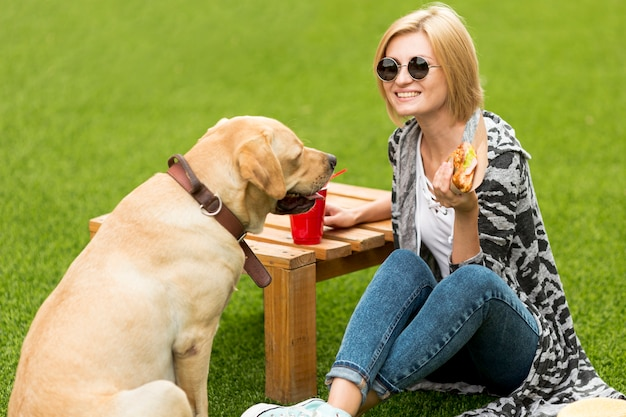 Dog looking at sandwich and woman smiling
