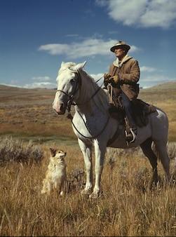 Dog man clouds sky landscape rancher horse