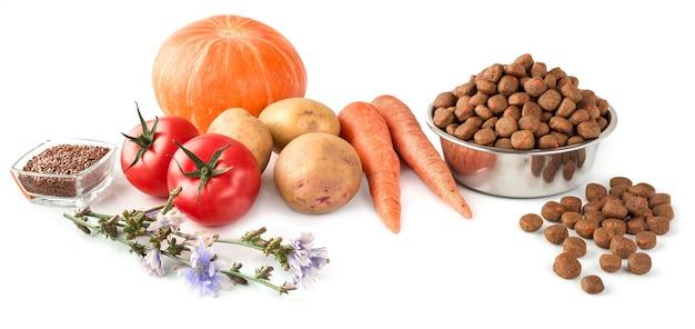 ペットショップについてのデザインのための白い背景の上の生野菜とステンレス皿の上の犬または猫の食べ物。