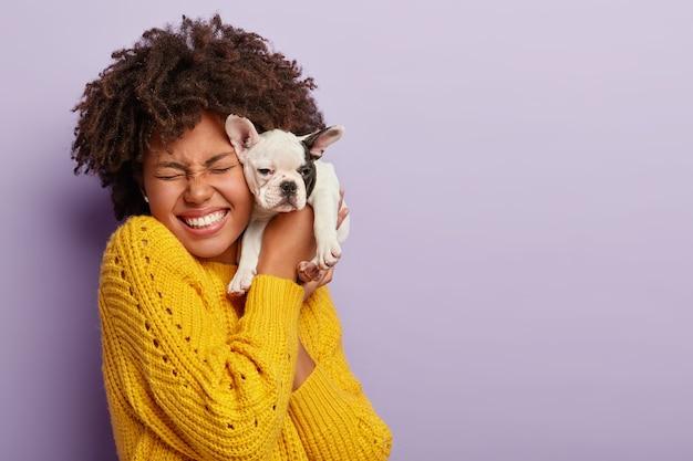 Proprietario del cane e il suo animale domestico. la ragazza riccia etnica felice tiene il piccolo cucciolo sveglio vicino al viso, esprime amore e cura per l'animale domestico, compra il cane della razza preferita, ride, ha gli occhi chiusi con piacere