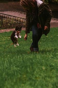 Владелец собаки играет с собакой в парке