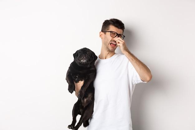 犬の飼い主は目を細めて嫌な臭いから鼻を閉じ、ベッドの匂いでパグを持って、白い背景の上に立っています