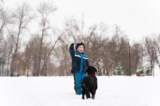 家族と雪の中で子供と遊ぶ犬
