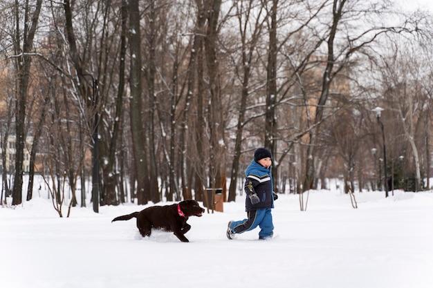 Cane che gioca con il bambino nella neve con la famiglia