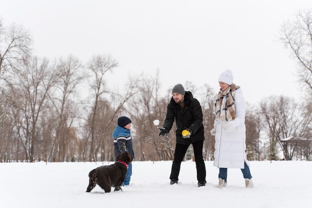 Dog playing with kid in the snow with family
