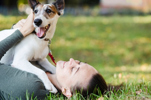 Dog playing with woman in grass