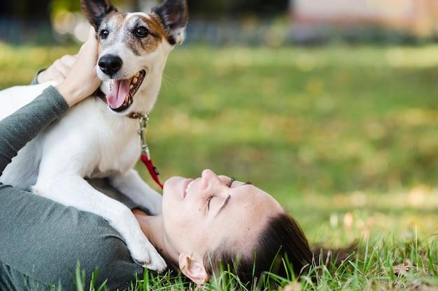 Собака играет с женщиной в траве
