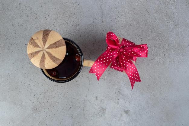 Tè alla rosa canina, un biscotto e un pacchetto regalo sul tavolo di marmo.
