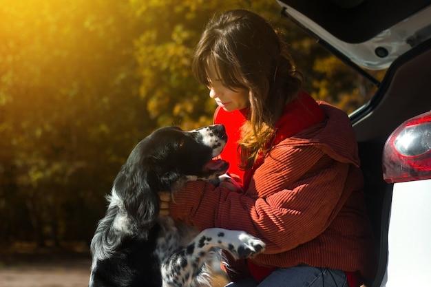 Dog russian spaniel leans against the woman mistress near the car on the street