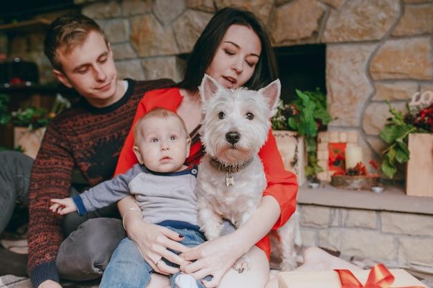 犬は家族の背景に木製の床に座って