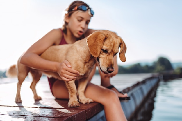 Dog standing on the river dock with girl