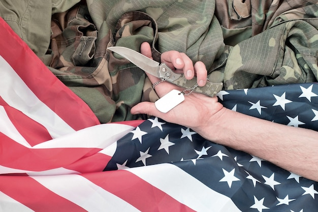 Жетоны лежат с рукой человека, который покончил жизнь самоубийством с ножом. представление о ветеране, который больше не может терпеть боль, решает покончить с собой