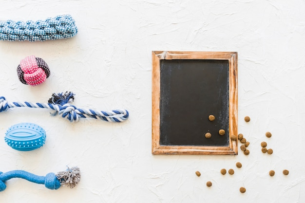 Dog toys near chalkboard and pet food