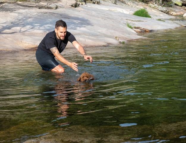 ラグーンで泳ぐために羊毛の子犬に教える犬のトレーナー。湖で泳ぐことを学ぶ茶色の子犬。