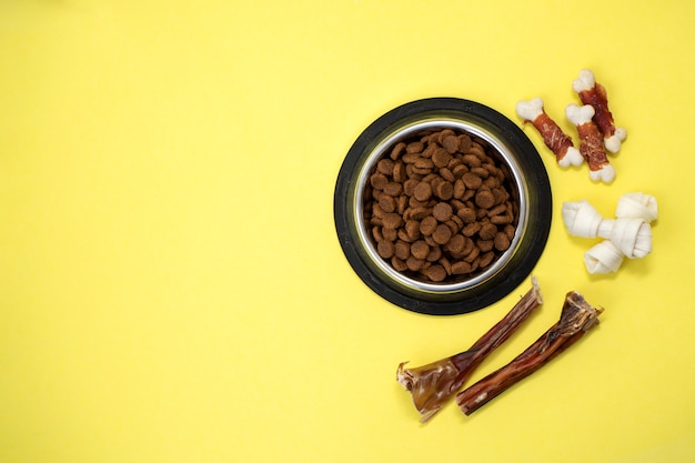 Dog treats and dry feed in bowl with copy space