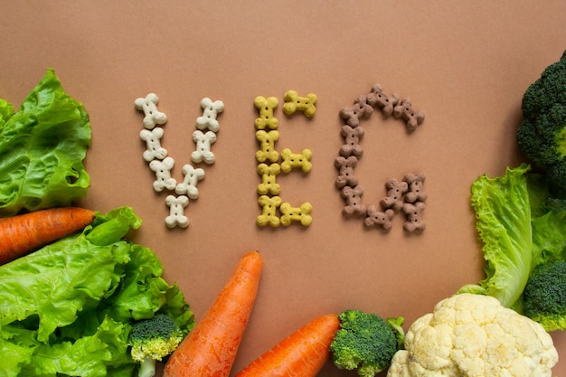 Dog vegetarian dry crunchies in form of bone with vegetables on beige surface. lettering veg.