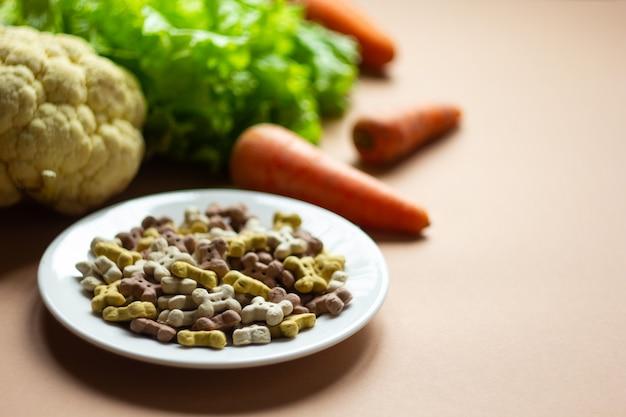 Собака вегетарианские сухие хрустящие сухарики на тарелке и свежие овощи
