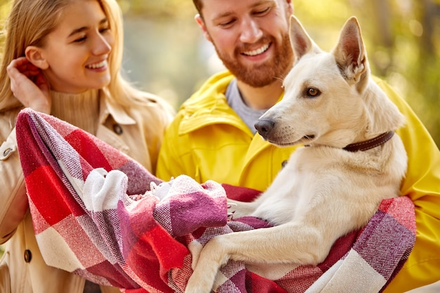 散歩で自然の中でカップルと犬、美しい夫婦は楽しんでいます