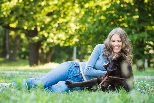 Dog with pet owner sitting in park
