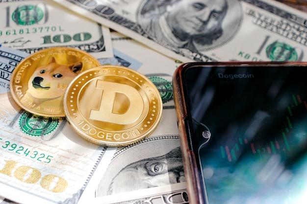 달러 지폐의 배경에 클로즈업된 dogecoin 동전, 그래프가 있는 전화