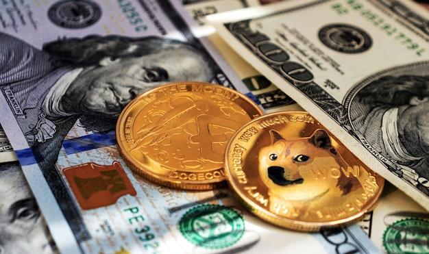 돈과 함께 클로즈업된 Dogecoin 동전, 많은 100달러 지폐 프리미엄 사진