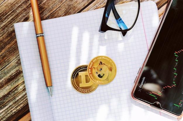 종이 상단 보기에 성장 그래프가 있는 dogecoin 동전