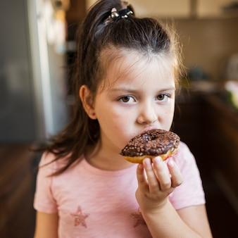 チョコレートdoghnoutを持つ女の赤ちゃん