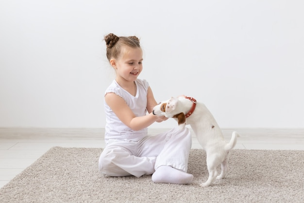 Dogs, children and pets concept - little child girl sitting on the floor with cute puppy
