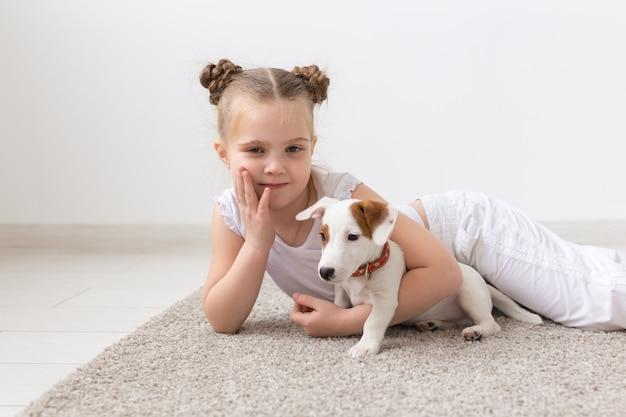 犬、ペット、動物のコンセプト-子犬ジャックラッセルテリアと一緒に座っている小さな子供の女の子。