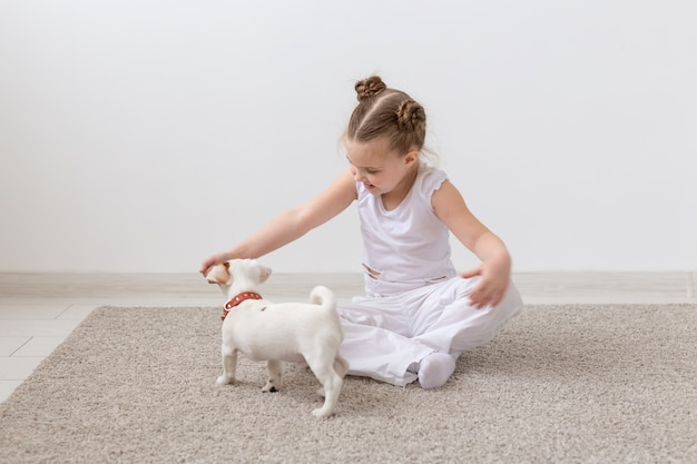 Dogs, pets and children concept - little child girl playing on the floor with cute puppy.