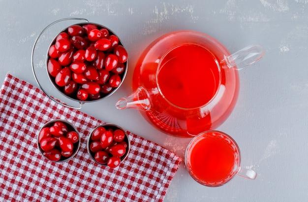 漆喰とピクニック布の上にドリンクを飲みながらバケツでハナミズキの果実
