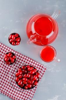 Bacche di corniolo con bevanda in secchi su intonaco e panno da picnic, vista dall'alto.