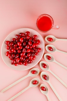 Bacche di corniolo con bevanda nel piatto e cucchiai di legno in rosa, vista dall'alto.