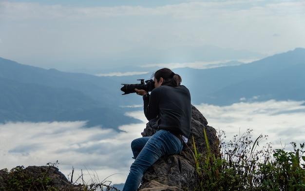アジアの男性写真家がdoi pha tanで山と濃い白い霧を撮影しています