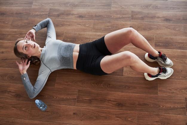 Занимаюсь абс. спортивная молодая женщина имеет фитнес-день в тренажерном зале в утреннее время